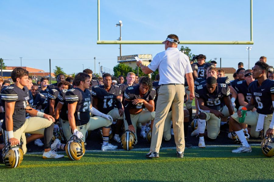 Simmons encourages the varsity football players with a pep talk before a game.