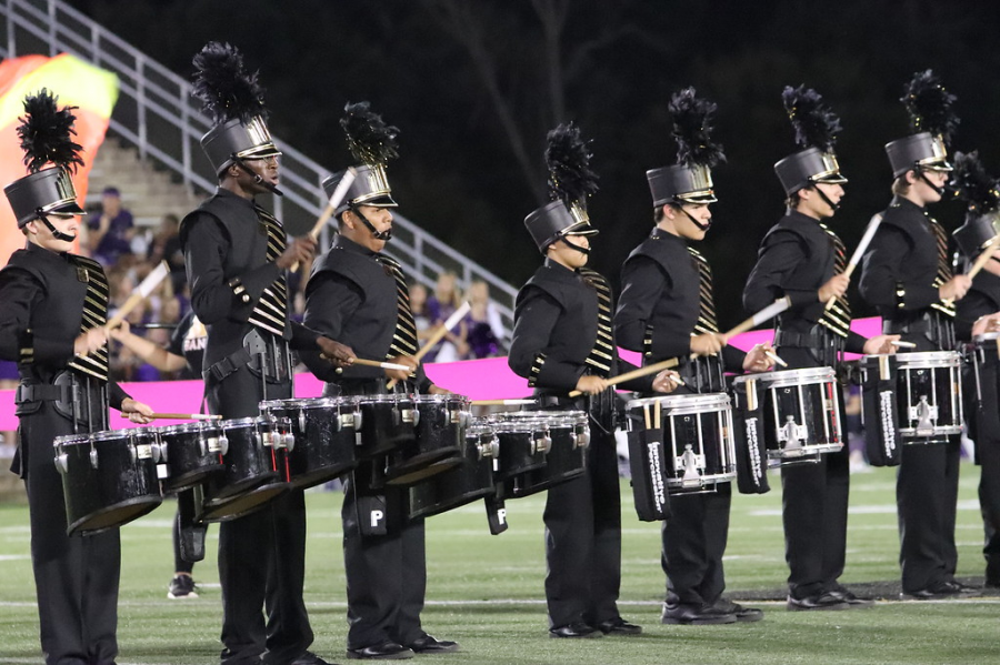 The Marching Band drumline performing during their show at halftime of a football game.