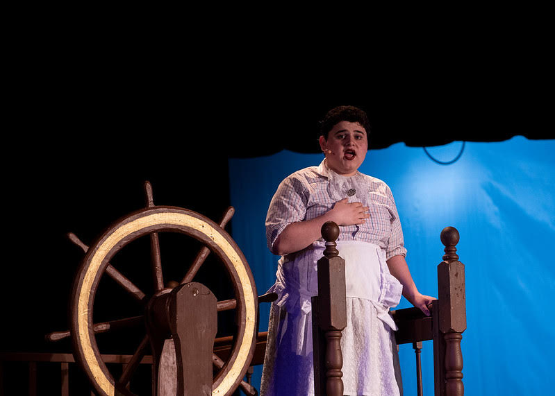 Alan Guiterrez starring as Betty Bumbrake in Peter and The Starcatcher, singing a lullaby perched next to a ship's wheel.