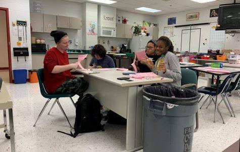 Hayleigh (Rowan) Ennis, 11, Katrina Mahoney, 11, Amelia Williams, 11, and Hannah Arnett, 11, trimming Valentine's Day themed bingo sheets.