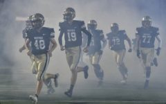 The varsity football team runs out onto the field. Photo Courtesy of Fred Ingham (delbray.com)