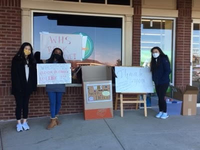 This is a photo of international club members holding signs for the book drive.