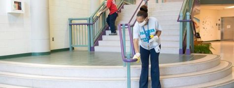 Custodians sanitize the handrails on a stairwell in a school.