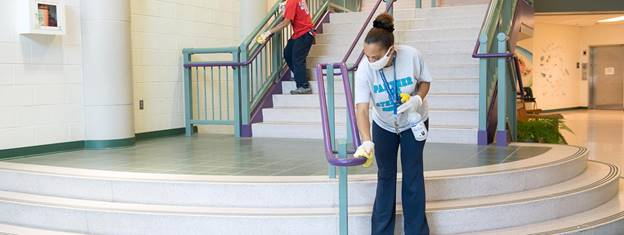 Custodians+sanitize+the+handrails+on+a+stairwell+in+a+school.